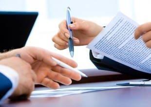 Руки с ручками на фоне бумаг