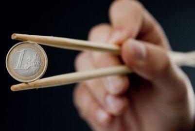 Мужчина держит монету в 1 евро китайскими полочками
