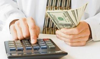 Мужчина подсчитывает прибыль на калькуляторе