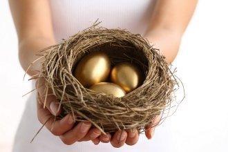 Девушка держит в руках птичье гнездо с золотыми яйцами