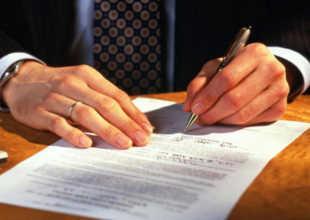Мужчина рукой подписывает бумагу
